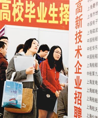 上海展览中心,求职者在长三角地区春季人才交流洽谈会暨2019届高校毕业生择业招聘会上了解岗位信息。