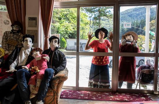 一名游客在社区中心做着鬼脸与人偶合影(图源:《纽约时报》)