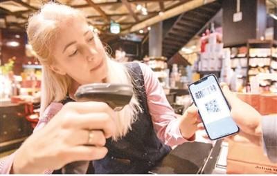 在奥地利维也纳,一名咖啡店员工扫描顾客的支付宝支付二维码。新华社记者 郭 晨摄