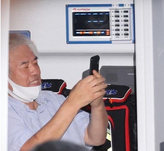 """""""爱第一""""教会牧师全光勋确诊后,在救护车上开心玩手机。(韩联社)"""