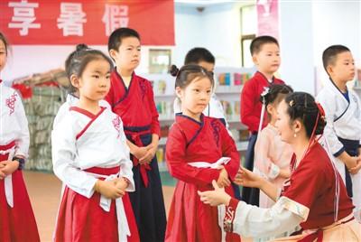 8月10日,在江苏省如皋市少儿图书馆内,老师在教小朋友学习汉服礼仪。徐慧摄(人民视觉)