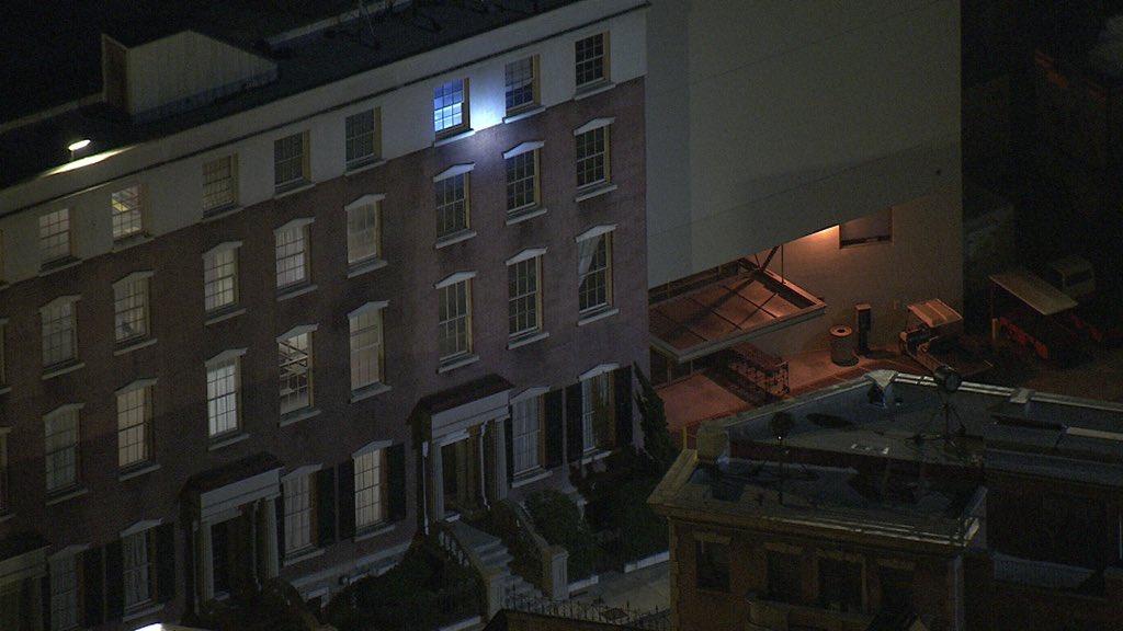 警察将灯光对准建筑高层的一扇窗户。(图源:推特)