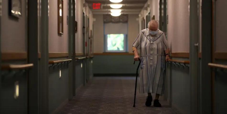 美国一家养老院中,一位戴口罩的老人走过。(图源:Getty)