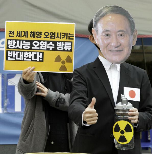 环保活动人士19日表演节目,称日本首相菅义伟认为手拿着福岛核污水是安全的。(韩民族日报)