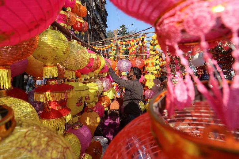 印度小贩在市场上挂灯笼(图源:路透社)