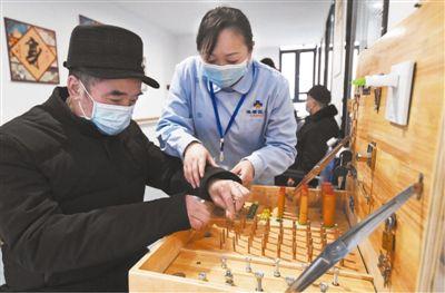 近日,一位老人在重庆渝北区仙桃街道空港佳园社区养老服务站工作人员的协助下进行手指功能训练。新华社记者 王全超摄