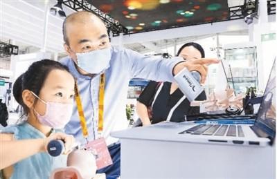 9月4日,在北京儿童医院展台,工作人员为小朋友介绍5G联网人工智能婴幼儿气道管理远程预警会诊系统。新华社记者 张玉薇摄