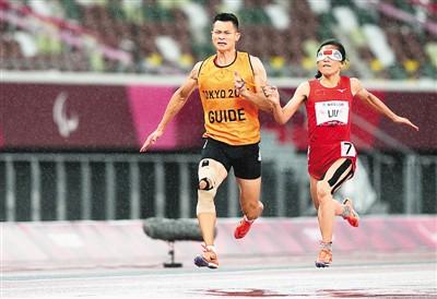 9月4日,在东京残奥会田径女子200米T11级决赛中,中国选手刘翠青获得金牌。图为刘翠青(右)和领跑员徐冬林在比赛中。新华社记者 熊 琦摄