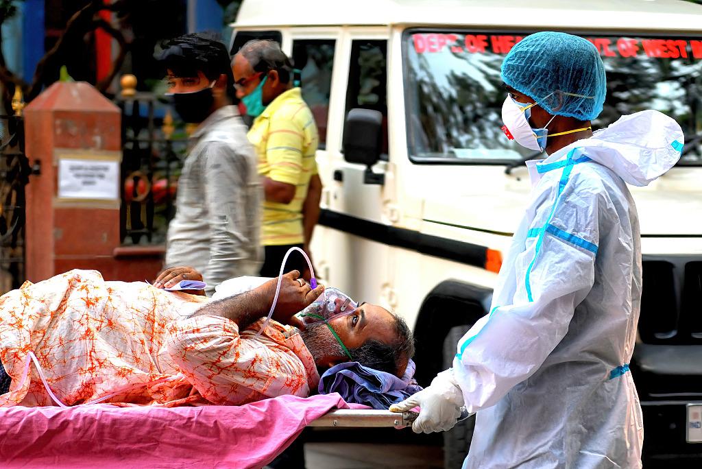 印度医护人员运送一名感染新冠病毒的患者。