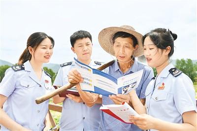 6月17日,湖北省咸宁市通城县税务局工作人员把税收政策送到田间地头。刘建平摄(人民视觉)