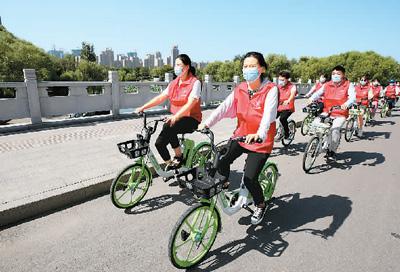"""山东省枣庄市龙山路街道青年志愿者在城区道路上骑共享单车开展""""低碳生活 绿建未来""""宣传活动。孙中喆摄(人民图片)"""