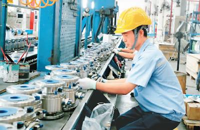 图为10月9日,位于江苏省苏州市的苏州纽威阀门股份有限公司员工在车间对阀门安装上压板。